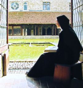 nun praying in the cloister